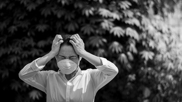 Menina asiática, sentindo a tensão e vestindo uma máscara. - proteção contra vírus, infecção, escape e emissões industriais.