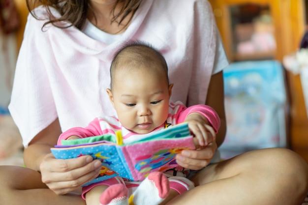 Menina asiática sentou no colo da mãe e lendo um livro de histórias para crianças