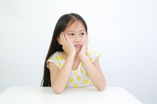 Menina asiática séria com o queixo apoiado nas mãos