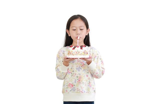 Menina asiática soprando velas em um bolo de feliz aniversário isolado