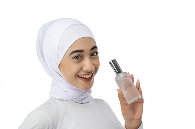 Menina asiática sorridente com hijab usando um vestido branco segurando um frasco de soro para tratamento facial