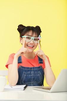 Menina asiática sorridente com topnots, em copos coloridos, sentado na mesa com o laptop