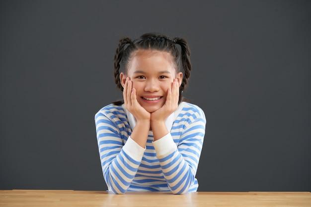 Menina asiática sorridente com tranças, sentado à mesa com as mãos nas bochechas