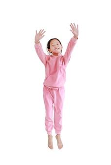Menina asiática sorridente com um agasalho esportivo rosa ou uma roupa esportiva pulando no ar isolado no branco