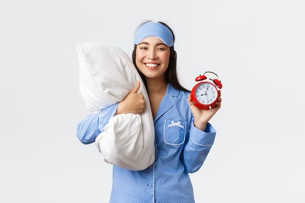 Menina asiática sorridente, entusiasmada e feliz, de pijama azul e máscara de dormir, mostrando despertador e