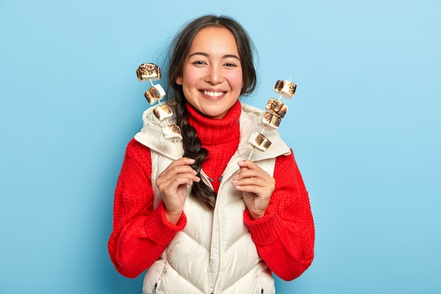 Menina asiática sorridente feliz segurando palitos com deliciosos marshmallows assados aromáticos, gosta de fazer um piquenique no campo e usa roupas quentes