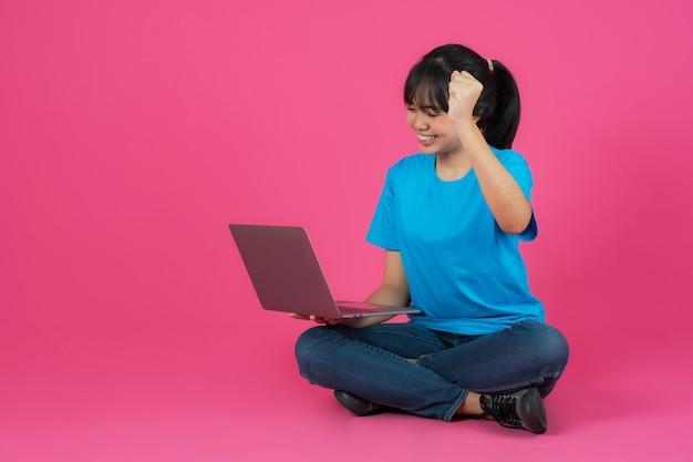 Menina asiática sorridente feliz usando laptop em fundo rosa
