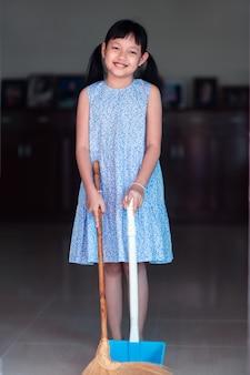 Menina asiática sorridente varrendo a casa com vassoura e pá de lixo