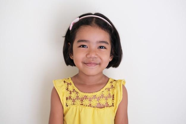 Menina asiática sorrindo com naturalidade enquanto olha para a câmera