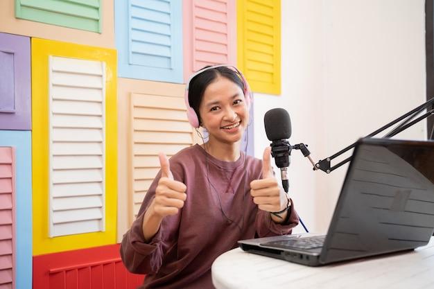 Menina asiática sorrindo em frente ao microfone enquanto grava o videoblog com o polegar para cima