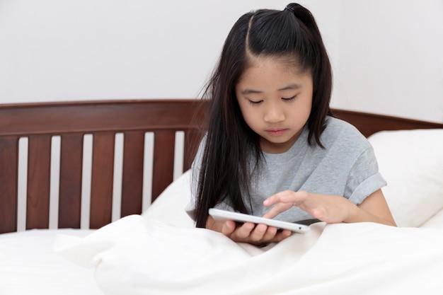 Menina asiática sorrindo nas mãos segurando e jogar tablet na cama no quarto. menina divirta-se com o tablet na cama. menina asiática olhando e jogando tablet.