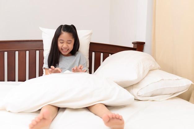 Menina asiática sorrindo nas mãos segurando e jogar tablet na cama no quarto. menina gosta e engraçada com tablet na cama. menina asiática olhando e jogando tablet.