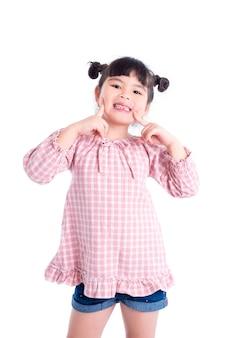 Menina asiática sorrir e mostrar sua primeira perda de dentes sobre fundo branco