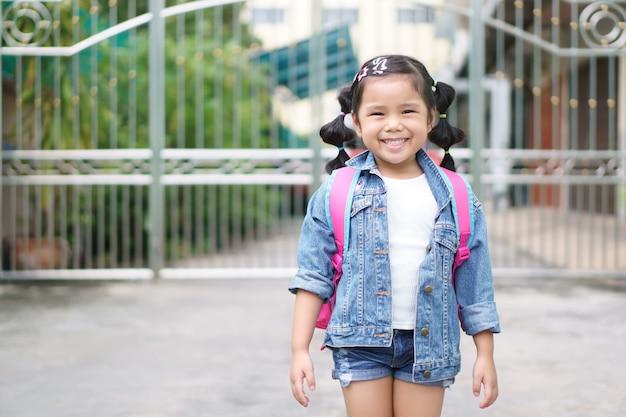 Menina asiática sorriso e estudante estilingue ou ombro rosa mochila