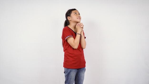 Menina asiática suplicando desejo isolado fundo branco