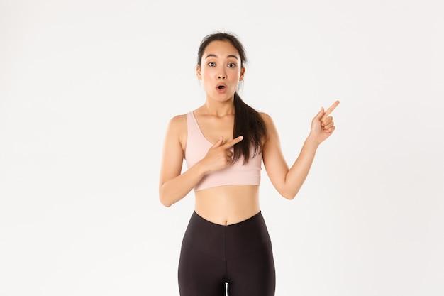 Menina asiática surpresa e espantada com roupas de fitness, apontando o dedo no canto superior direito, ofegando e dizendo uau impressionada.
