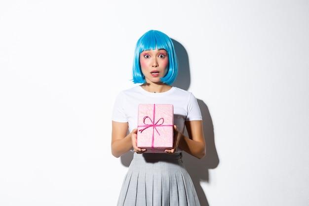 Menina asiática surpresa na peruca de festa azul, olhando para a câmera confusa, segurando a caixa de presente, de pé.