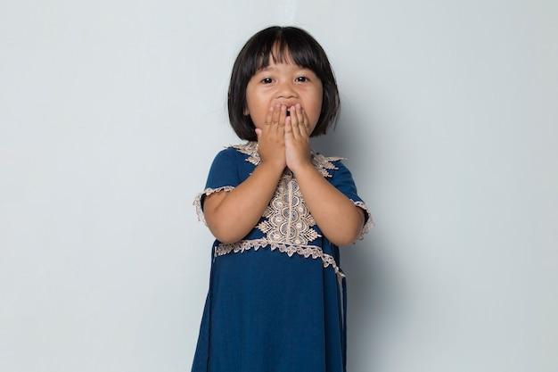 Menina asiática tapando a boca com a mão, sentindo-se surpresa com alguma coisa