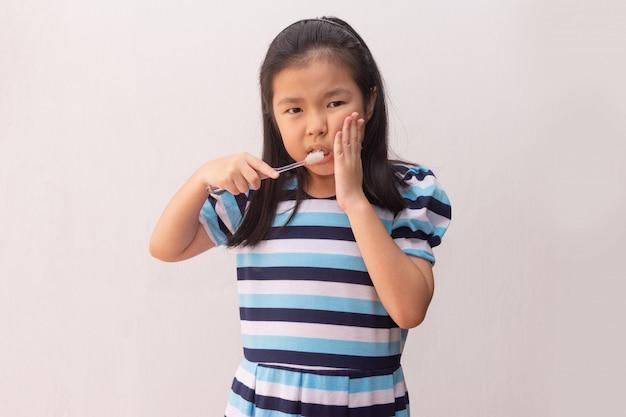 Menina asiática tem uma dor de dente segurando a escova de dentes