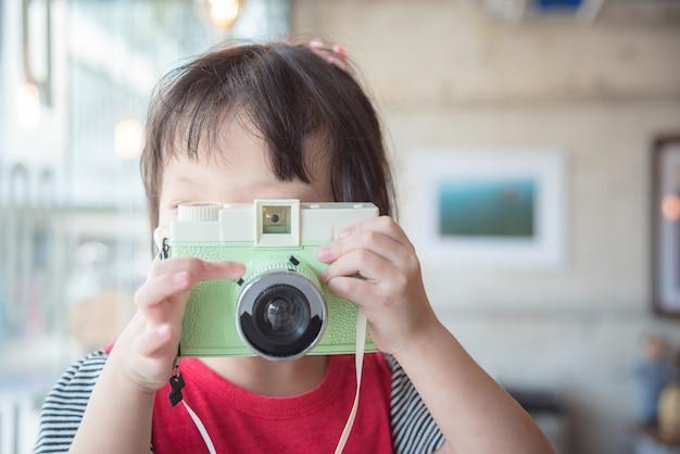Menina asiática tirando foto pela câmera clássica no café