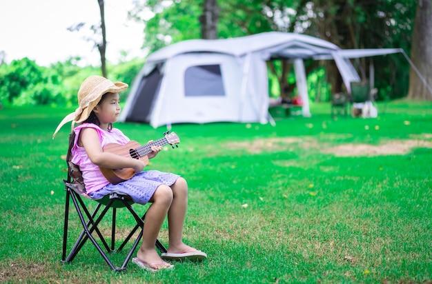 Menina asiática tocando ukulele ou guitarra havaiana no parque enquanto acampa no verão