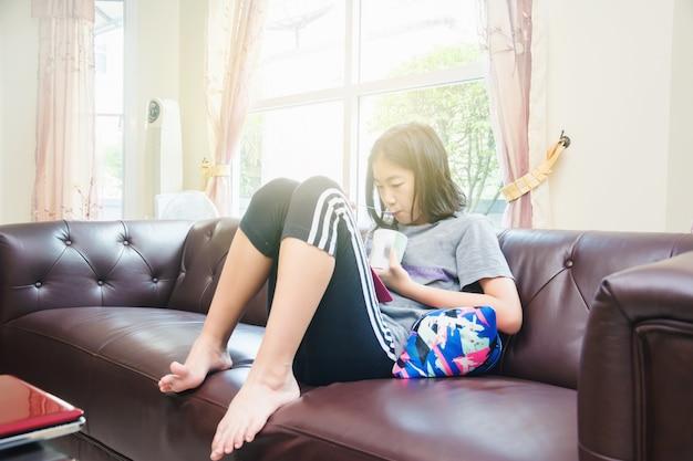 Menina asiática tomando café da manhã, pequena tigela de cereais e leite e olhando para o telefone inteligente na manhã
