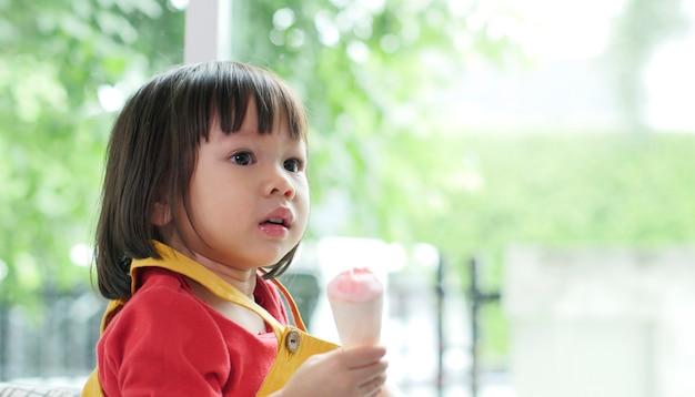 Menina asiática tomando sorvete em um cone crocante