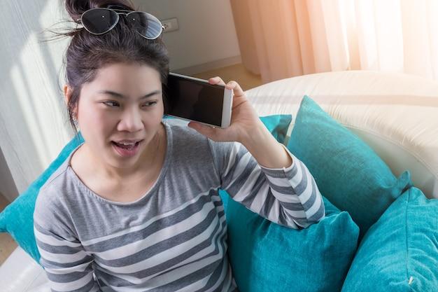 Menina asiática trabalhando com smartphone sofá aconchegante e casual no quarto