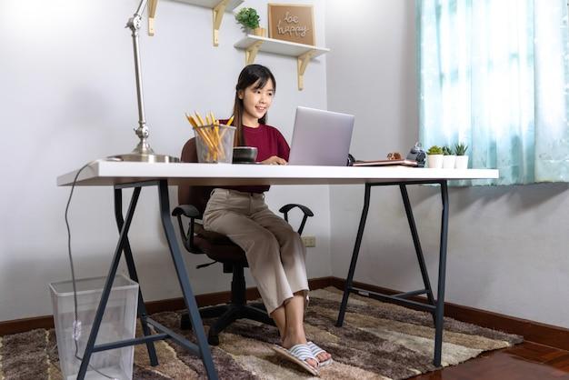 Menina asiática trabalhando remotamente em casa