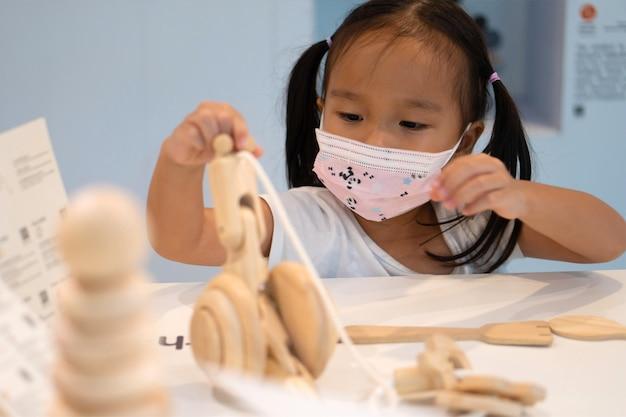 Menina asiática usa máscara facial para prevenir o coronavirus 2019 (covid-19) e brinca de brinquedo em escolas.