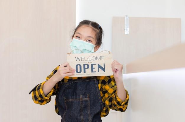 Menina asiática usando avental, sorrindo, sorrindo e segurando uma placa de madeira aberta