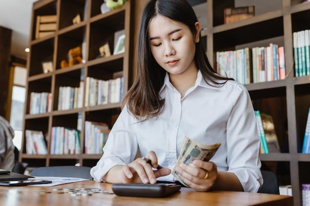 Menina asiática usando calculadora para contabilidade pessoal