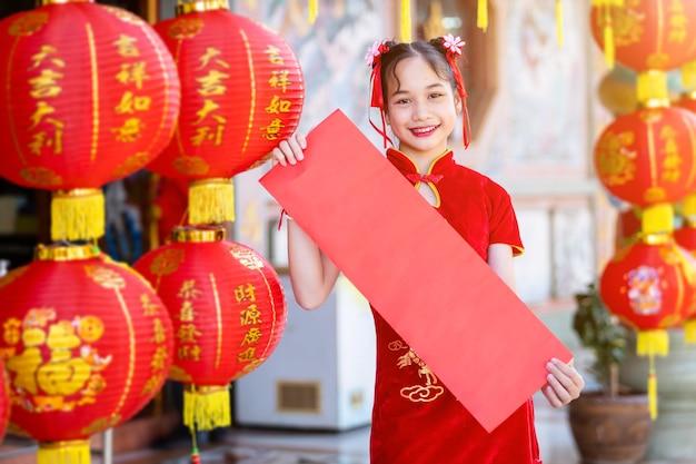 Menina asiática usando cheongsam chinês tradicional vermelho, mostra papel em branco vermelho e lanternas com o texto chinês bênçãos escrita nele é uma bênção da fortuna para o ano novo chinês
