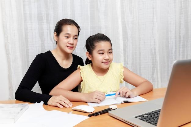 Menina asiática usando lápis para fazer o dever de casa com a mãe