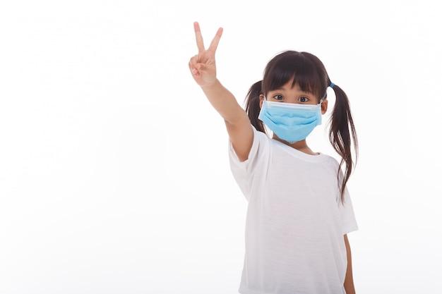 Menina asiática usando máscara com dois dedos para cima