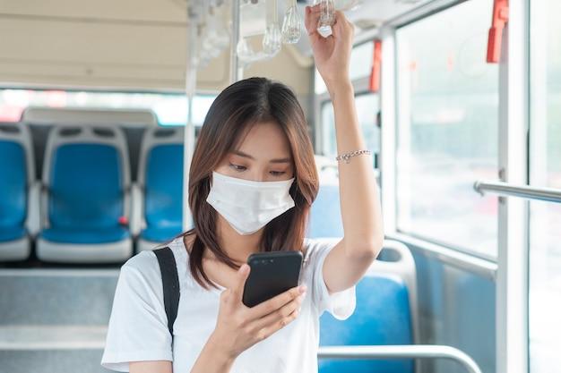 Menina asiática usando máscara enquanto usa smartphone no ônibus