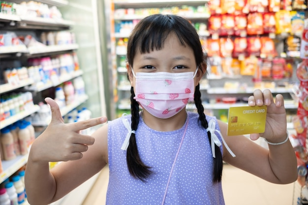 Menina asiática usando máscara facial e mostrando o cartão de crédito