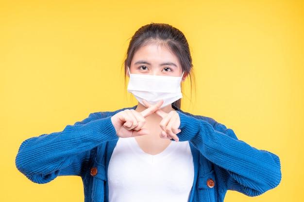 Menina asiática usando máscara facial mostra gesto com as mãos para parar surto do vírus corona
