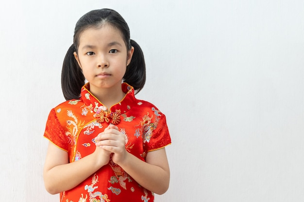 Menina asiática usar cheongsam com gesto de parabéns, reunir as mãos em saudação. no ano novo chinês