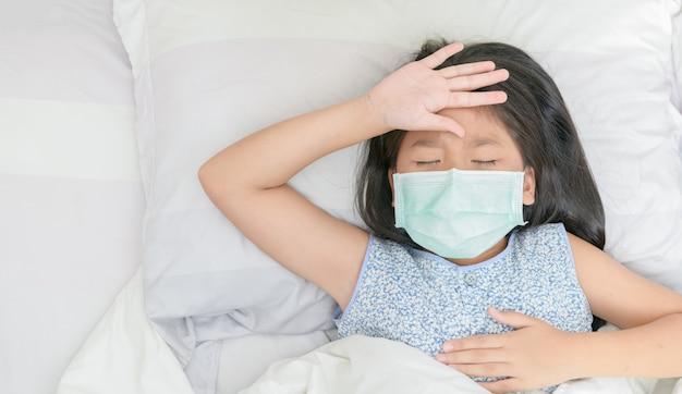 Menina asiática usar máscara cirúrgica tem febre alta e dor de cabeça.