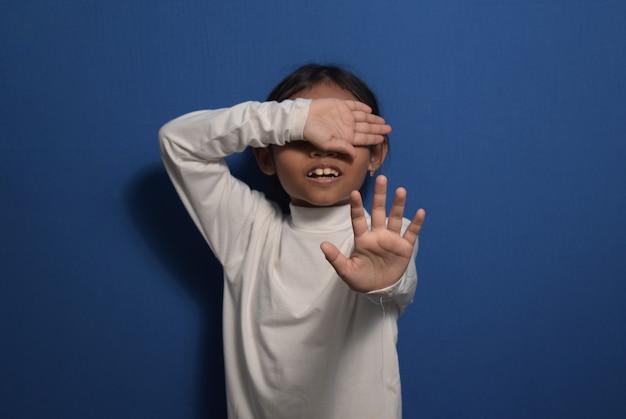 Menina asiática vestindo camiseta branca com a mão estendida sinalizando para impedir a violência infantil