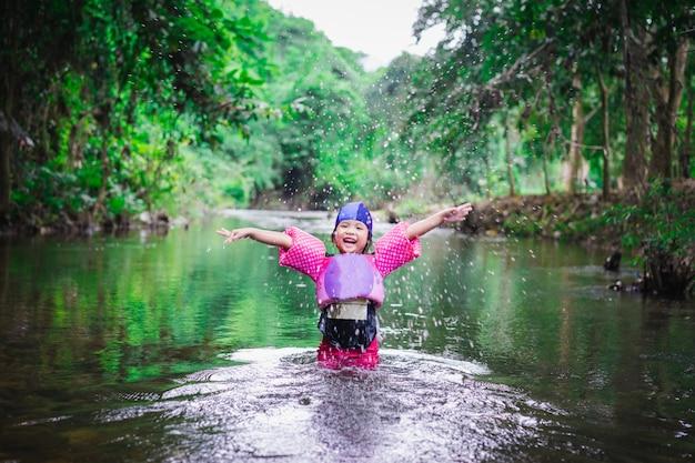 Menina asiática vestindo mangas infláveis, jogando na água da natureza de férias
