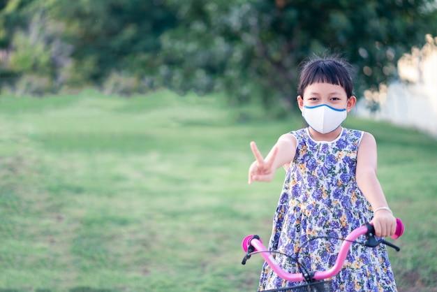 Menina asiática vestindo máscara facial e andar de bicicleta lá fora com sorriso e feliz