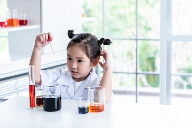 Menina asiática, vestindo um uniforme branco de cientista
