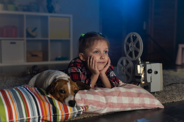 Menina assistindo a um filme antigo em um projetor de filmes retrô vintage com um cachorro