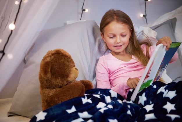 Menina assistindo a um livro ilustrado com um ursinho de pelúcia