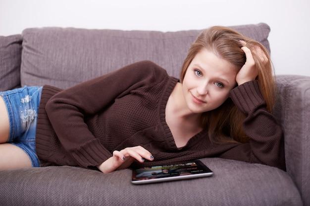 Menina assistindo séries de tv e filmes pelo serviço de streaming em casa no tablet digital