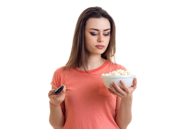 Menina assistindo tv e segurando um prato com pipoca isolada no fundo branco