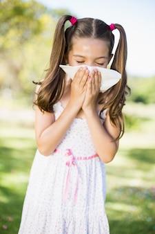 Menina assoar o nariz com lenço enquanto espirra