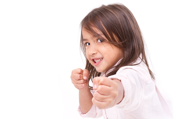 Menina assumindo postura, praticando artes marciais